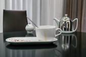 koszos csésze tea után, foltokkal és desszerttel a konyhaasztalon.