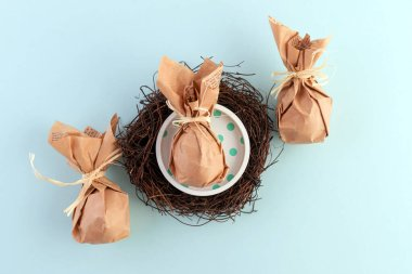 Easter table decor: a set of eggs wrapped in eco-friendly packaging in a nest of dry branches. Close-up