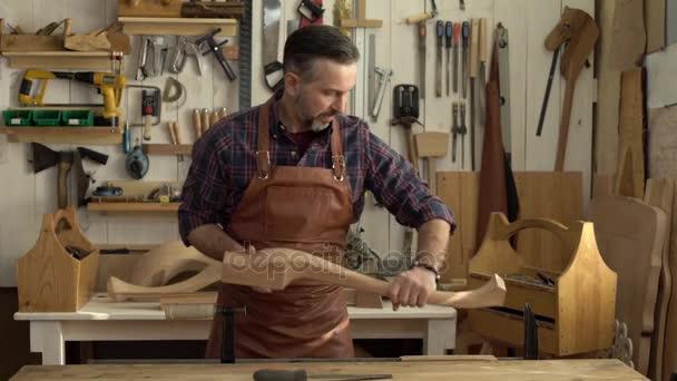 CAB Maker začíná jeho/Cabinet-maker pracovní den přichází do svého truhláře bere nohy stolu cabrioli a začíná pracovní