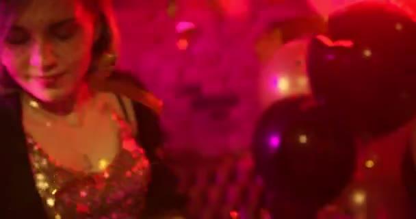 Tančí v mladých žen konfety/Happy dancing energicky v nočním klubu. To může být Novoroční večírek nebo narozeninovou oslavu, konfety létají všude kolem nich