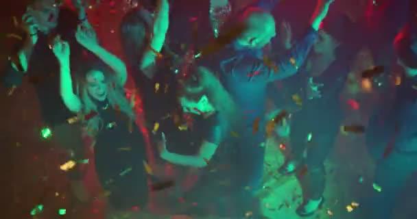 Tanzen in einem Nachtclub. Hohen Winkel Schuss/Jugendliche tanzen in der Diskothek. Konfetti sind überall um sie herum. Sie sind Freunde, feiern, Geburtstagsparty oder ein neues Jahr