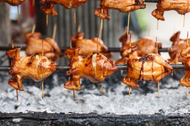 Roast whole chicken on rotating charcoal stove