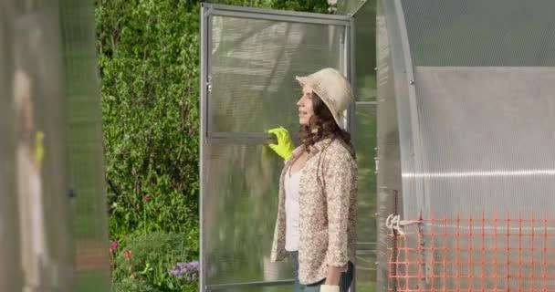 Krásná dívka v klobouku pracuje na zahradě, vychází ze skleníku. Mladá farmářka otevírá dveře skleníku. Dělník pracuje v soukromé domácnosti. Gardener je spokojený s její prací ve slunečný den