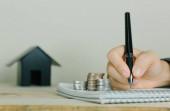 Immobilieninvestitionen und Auto Hypothek Finanzkonzept, Hand legt Geld Münzstapel mit Holzhaus.