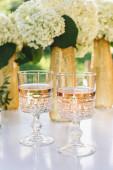 Rosenwein im Glas. Rosenwein auf goldenem Flaschenhintergrund mit Blumen