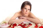 Closeup krásná, mladá a zdravá žena ve spa salonu na bambusových rohožích s okvětními lístky růží. Wellness, zdraví a uzdravení koncept.