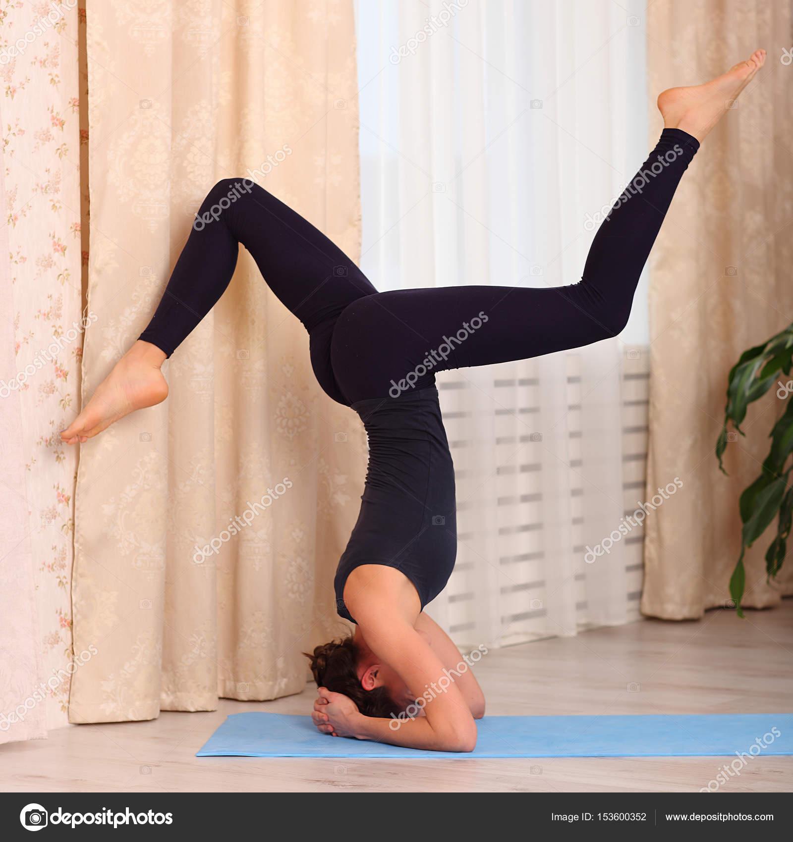 Yoga zu Hause. Attraktive Frau macht Yoga am Morgen nach Hause ...