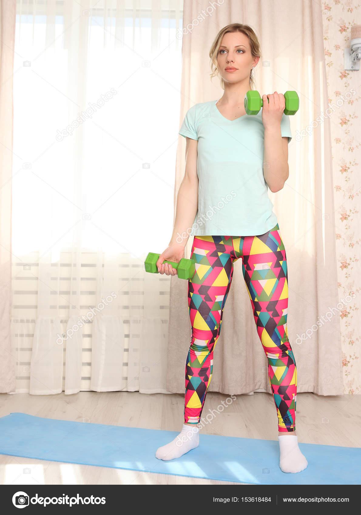 f5e649a2786e6 Atractiva mujer rubia hacer ejercicio de gimnasio en casa sobre una  alfombra azul — Foto de ...