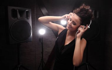 woman in black dj with white headphones listening to the music.