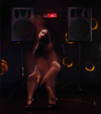 sexy young girl with perfect body and ass dance gogo near two big black speakers. slow sync flash technique