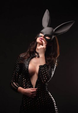 Sexy woman with large breasts wearing a black bunny mask standing on dark background.