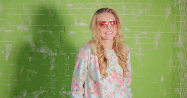 Blonde beautiful woman in sunglasses posing.
