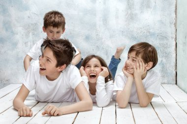 Happy four children posing together , wearing jeans and white shirts, smiling. stock vector