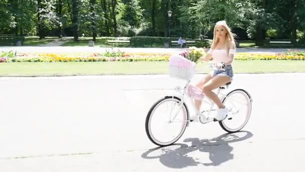 Kavkazské blondýnku na slunečný den na kole v městském parku.