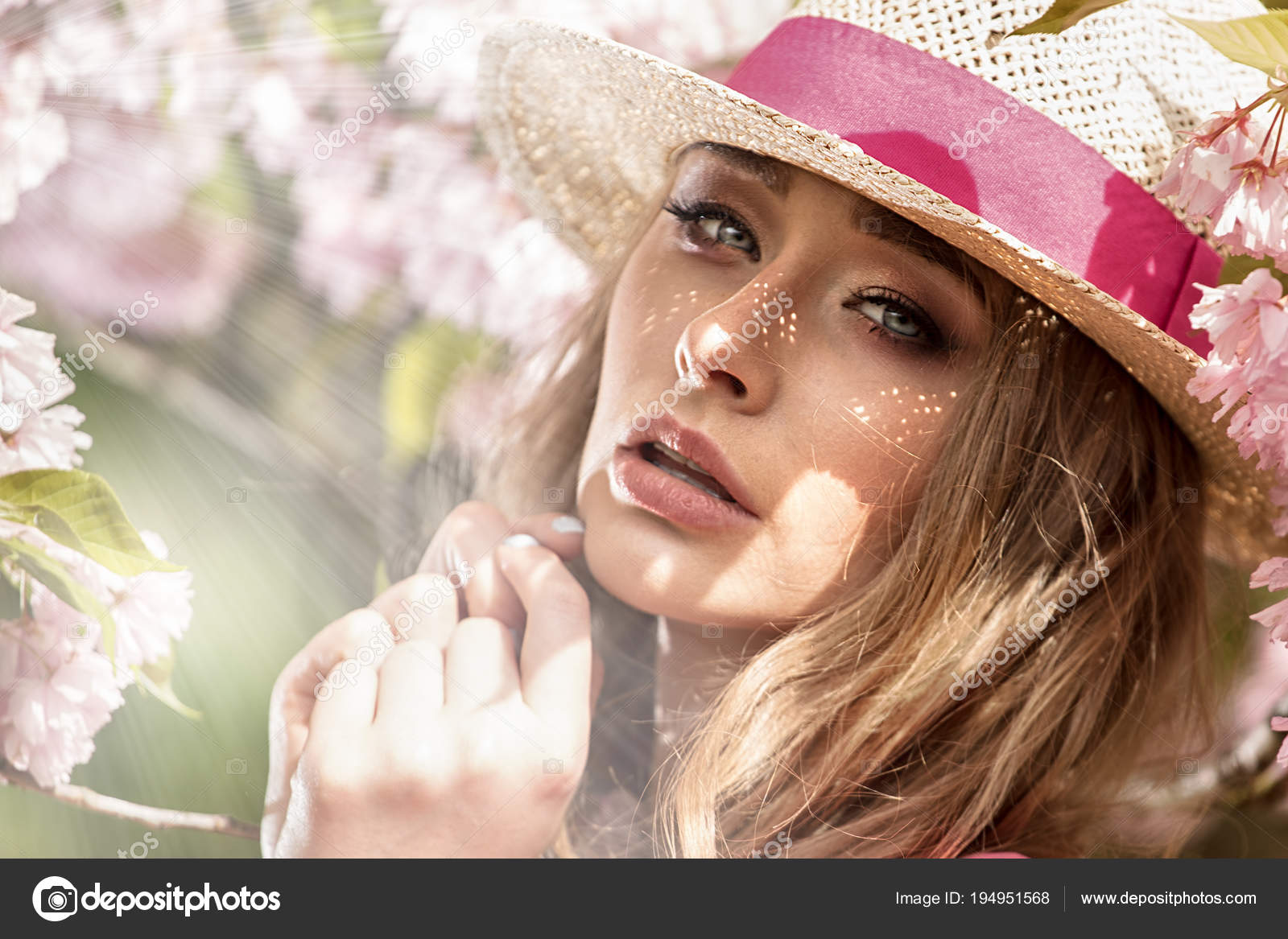 Bonita caucasiana loira atraente posando em Primavera flor flores  desabrochando jardim. Dia de sol. Menina com chapéu elegante na cabeça. 5407b1f7897