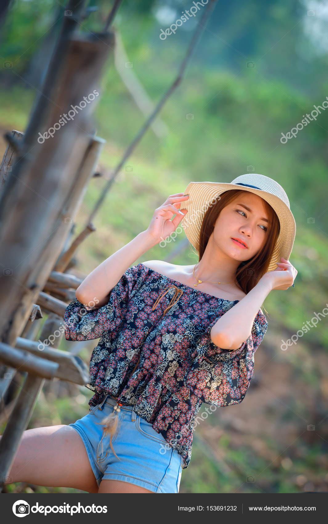 Mujer de Asia fuera hombro camisa y pantalones vaqueros cortos de pie hat  en naturaleza — Foto de thegoatman 537981fba33