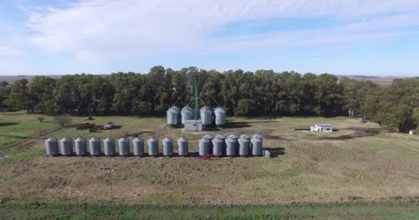 Aerial drone scene of large line os silos in the countryside and trees as wind shield. Camera pan to top view. Buenos Aires, Argentina.