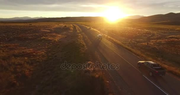 Letecká drone scéně trasy ve stepní krajina při západu slunce zlaté hodiny. Fotoaparát kupředu, auto a kolo na silnici. Patagonia Argentina, Junin de los Andes. Hora na pozadí