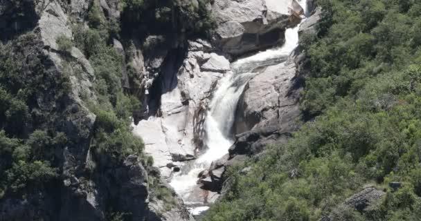 Waterfall at old eroded rocky basin between woods. Quebrada del Condorito National Park, Cordoba, Argentina