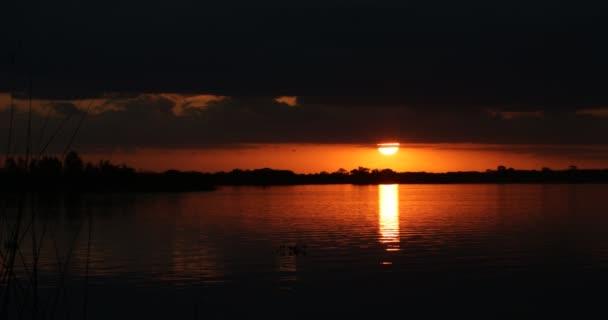Természetes parti táj naplementekor. A Nap visszaverődik a víz felszínén, miközben egy felhő mögül tűnik fel. Vízáram mozgása az ég színes kontrasztos tükröződéseivel