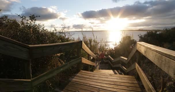 Young woman climbing wooden urban stairs at natural seashore landscape. She sitts at railing staring the sunset at horizont. Piriapolis, Uruguay