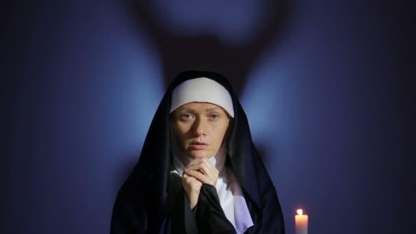 Halloween. jeptiška se modlí. stíny v podobě ďábla. vymítání ďábla