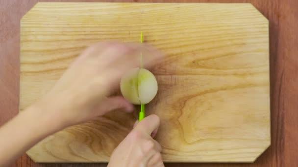 Cibule v kuchyni připravuje šéfkuchař žena. pohled shora