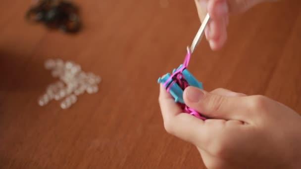 malá holčička plést náramek z gumiček. Barevné gumičky pro tkaní