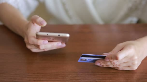woman makes a purchase using a smartphone and a bank card.