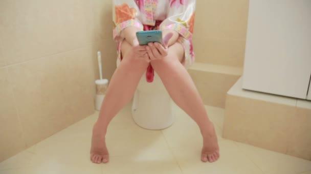 žena sedí na WC v koupelně. pomocí chytrého telefonu. domácí župan