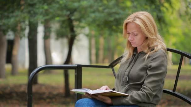 Blonde Frau liest Buch am Graben im Herbstpark.