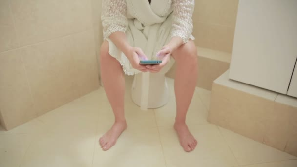woman sitting on toilet in the bathroom. using smartphone. home bathrobe