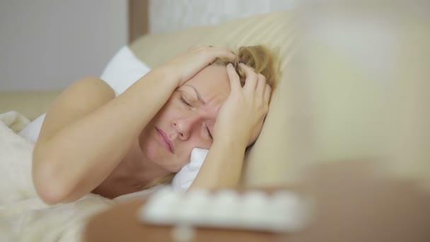 kranke Frau auf dem Bett liegend. Pillen und ein Glas Wasser. Tabletten zu trinken. Schmerzmittel