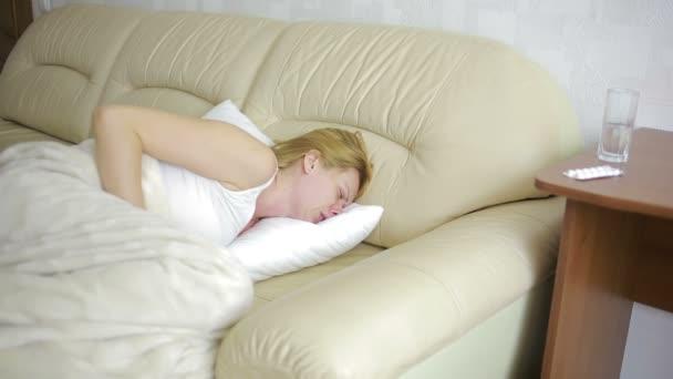 žena s bolestí břicha, ležel na pohovce. Dívka pití prášky proti bolesti