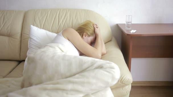 kranke Frau auf dem Bett liegend. Pillen und ein Glas Wasser. Trinktabletten. Schmerzmittel