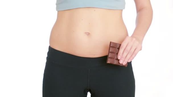 Mädchen einen Apfel und Schokolade zu essen. Diät-Konzept. Fett Bauch und dünne Taille