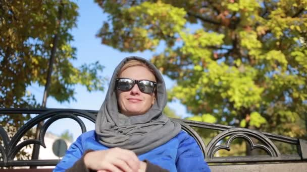 beautiful woman in sunglasses sitting on the bench in autumn park. Yellow leaves