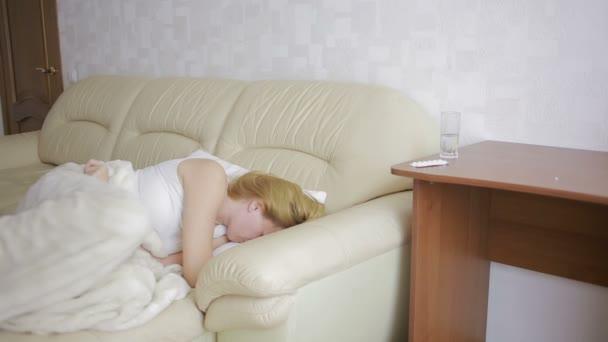 Frau mit Bauchschmerzen auf dem Sofa. Mädchen trinken Pillen Schmerzmittel