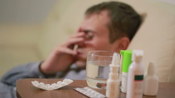 kranker Mann liegt im Bett leiden Virus mit Medikamententabletten. Trinkpille