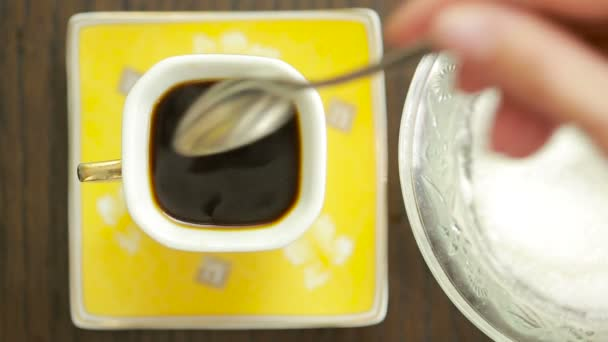 Coffee cup detail and teaspoon. Pouring sugar on coffee cup. top view
