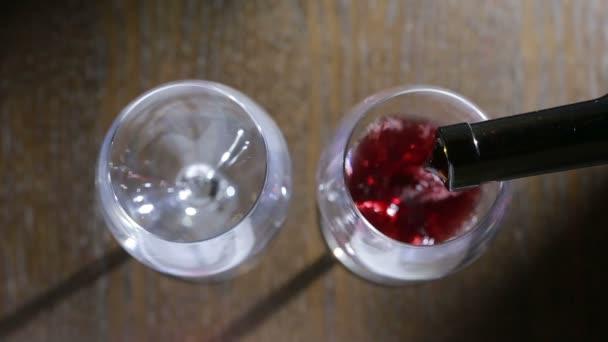 két pohár vörös bort önteni. felülnézet. Férfi és női kezek