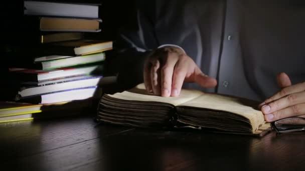 Kluger Mann, der spät in der Nacht lernt, sitzt am Schreibtisch und liest Buch