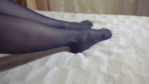 Dívka obléká punčochy na posteli v ložnici. detail
