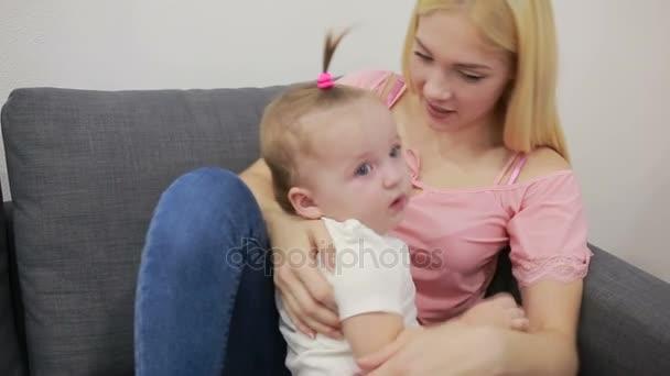 matka s dítětem hrát na pohovce v obývacím pokoji