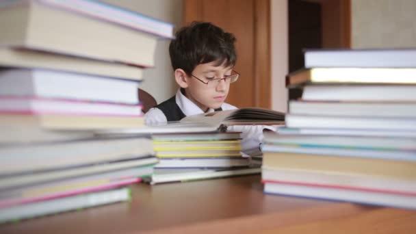 chlapce, který seděl u stolu s hromadou knih. dětského čtenářství. chlapec s brýlemi