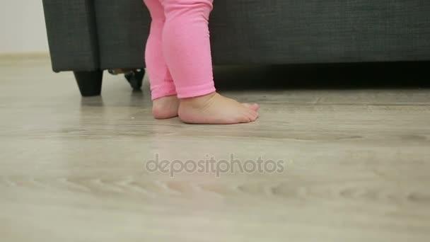 malá holčička chodí naboso ve svém obývacím pokoji
