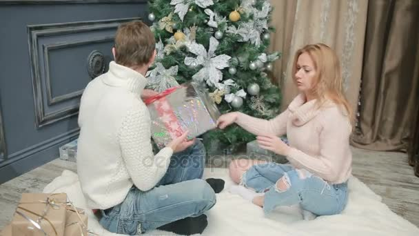 young married couple arranges gifts under the christmas tree stock video