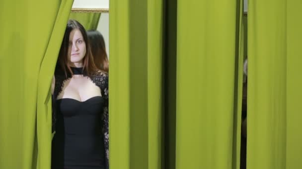 happy pretty young woman trying on clothes in dressing room of clothing shop