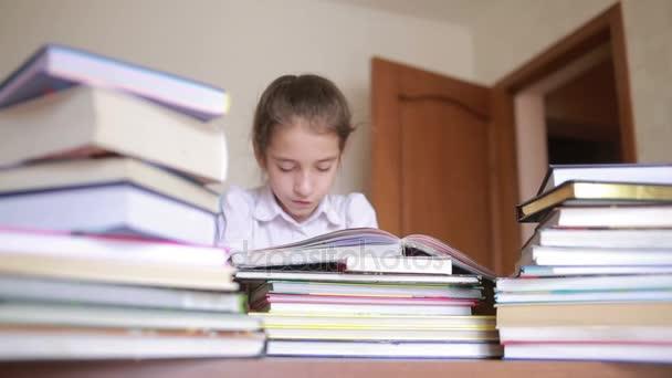 malá holka ve školní uniformě čte knihu, sedí mezi hromadami knih