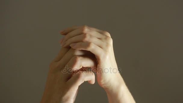 Chiuda in su commovente che tiene insieme su fondo vago della mano di uomo e donna